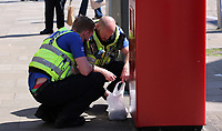 Pictured: Two police officers examine an unattended package left by a post box in Union Street, Swansea Wednesday 24 May 2017<br /> Re: The Quadrant shopping centre in Swansea has been evacuated following reports of a suspicious package being found.<br /> The bus station and Swansea Indoor Market have also been closed as part of the evacuation.