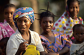 Ujiji, Tanzania. Woman in brightly coloured cotton turban with other women behind.