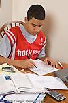 teenage boy age 15 homework working in kitchen vertical