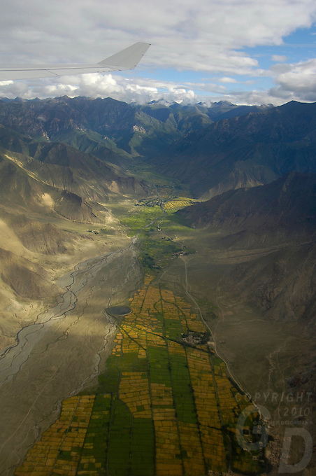 Aerial on the approach to Lhasa Tibet, view from a commercial airliner, approximate 15 minutes before Lhasa,in the foreground farm, land.