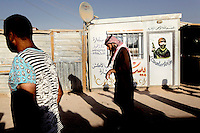 Two men walk past a portacabin with a mural of an armed man on its door. Approximately two million people have fled the conflict in Syria. At least 130,000 of them live in Zaatari Refugee Camp, although it was designed to house 60,000, and a further 2,000 people arrive each day.