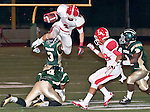 Orange Lutheran High School running back leaps over Damien High School defenders for a first down