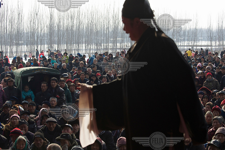 A traditional storyteller, watched by a large crowd, performs at the Ma Jie folk festival. <br /> <br /> For centuries farmers in Henan have gathered during Chinese New Year in the region's wheat fields to listen to bards singing and recounting old tales. <br /> <br /> Now storytellers come from all over China to attend the annual festival where large crowds gather to watch the best performers.