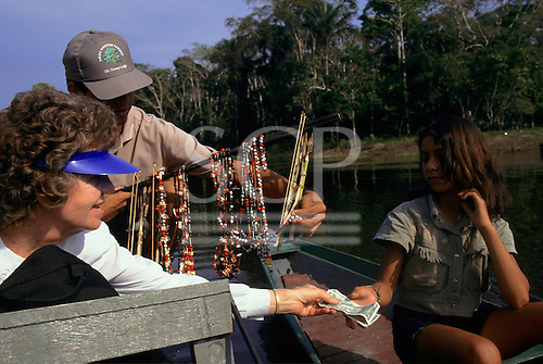 Ariau Lodge Hotel, Rio Negro, Amazonas State, Brazil. Tourists in a boat buying souvenirs of local bead jewellery from caboclo traders.