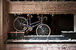 A bicycle Hanging from the ceiling in back of an abandoned hotel's front counter