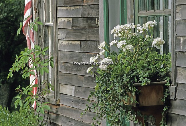 Flower box on an old, unpainted building in Georgetown, Maine, USA with American flag showing.