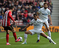 (L-R) Javier Manquillo of Sunderland passes the ball past Kyle Naughton and Fernando Llorente of Swansea City during the Premier League match between Sunderland and Swansea City at the Stadium of Light, Sunderland, England, UK. Saturday 13 May 2017