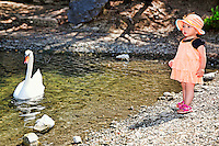 A pretty little girl with hat having fun with a swan