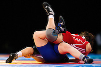 11 DEC 2011 - LONDON, GBR -  Maja Erlandsen (NOR) (in red) tries to overpower Chloe Spiteri (GBR) (in blue) during their 72kg category repechage bout during the London International Wrestling Invitational and 2012 Olympic Games test event  at the ExCel Exhibition Centre in London, Great Britain (PHOTO (C) NIGEL FARROW)