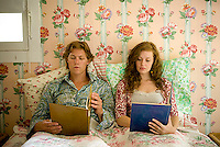 Young couple in bed in room with floral wallpaper