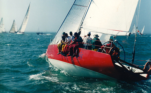 …..the sailing headgear which was the trademark of his famous grandfather Roy Dickson, seen here at the helm of his Corby 40 Cracklin Rosie at the start of the 1997 Fastnet Race. Photo: W M Nixon