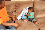 Baby boy 10 months old at home with father finding toy ball hidden under cloth