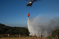 A helicopter from the Andalusian Service firefighting (INFOCA) drops water over scrub land during a forest fire in Los Barrios, near Cadiz on July 25, 2015. Since July 19 wildfires have ravaged nearly 39,000 hectares of land in Spain, according to the provisional figures from the agriculture ministry. . © Pedro ARMESTRE