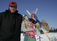 """Volunteer checker Jim Gallea poses with his cardboard """"Aloha"""" theme welcome sign Thursday at the halfway checkpoint of Cripple."""