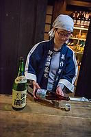 Japan, Okayama Prefecture, Katsuyama. Tsuji Honten Sake factory. Family run for seven generations, brother-sister team of President and Master Brewer. Maiko, master brewer pouring sake. MR