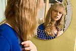13 year old teenage girl looking at self in mirror