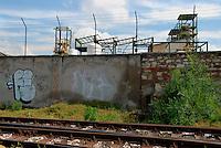 Brescia / Italia - giugno 2013<br /> Muro di cinta dell'industria chimica Caffaro, nel centro di Brescia. Alla base del muro vicino ai binari appare lo scarico attraverso il quale defluivano nell'acqua le sostanze inquinanti. Per 50 anni la Caffaro ha scaricato senza alcuna filtrazione ingenti quantità di PCB che hanno gravemente contaminato l'ambiente. Le autorità hanno posto sotto sequestro ampie aree agricole ed è proibito consumare i prodotti del suolo. La cancerogenità del PCB è nota dagli anni 30. Sulle conseguenze per la salute si stanno facendo studi epidemiologici sulla popolazione bresciana ma le autorità sanitarie hanno già segnalato una percentuale di tumori sensibilmente più alta di quella nazionale.<br /> Foto Livio Senigalliesi