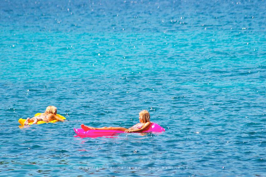 Two young women girls floating on inflatable air mattresses, yellow, pink, on a deep blue sea. Uvala Sumartin bay between Babin Kuk and Lapad peninsulas. Dubrovnik, new city. Dalmatian Coast, Croatia, Europe.