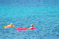 Two young women girls floating on inflatable air mattresses, yellow, pink, on a deep blue sea. Uvala Sumartin bay between Babin Kuk and Lapad peninsulas. Dubrovnik, new city. Dalmatian Coast, Croatia, Europe.