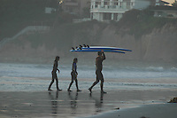 Pacific Beach, San Diego, California, USA:  Monday, January 19 2009.  A surf instructor carries two boards out iof the water near Tourmaline Street as two student surfers follow him.  The Martin Luther King Jnr Day holiday was marked by warm weather, big surf and a technicolored sunset as much of the rest of the country shivered in the cold.