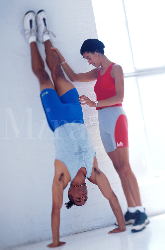 Personal training session woman assists man with his handstand.