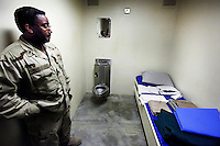 A military guard shows a display cell in the maximum security section at Camp Delta of the American naval base at Guantanamo Bay, where over 600 alleged al Qaeda members have been held indefinitely. Described by the US as 'unlawful enemy combatants', they were captured primarily in Afghanistan during the 'war against terror'.