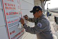 City Park & Recreation workers Peter Cruz an Cuauhtemoc Salis add ?No Alcohol? labels to beach entrances in Ocean Beach after a petition drive failed to gather enough valid signatures to overturn the one year trial beach alcohol ban, Wednesday January 16 2008.  While the ordinance is in effect immediately, San Diego Police Chief William Landsdowne has said that San Diego Police will most likely warn people during the next thirty days before they start issuing citations.