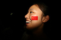 CHINA. Beijing. A woman smiles whilst watching the opening ceremony of the Beijing Summer Olympics. 2008