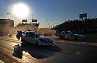 Sept. 23, 2011; Ennis, TX, USA: NHRA funny car driver Tim Wilkerson (near lane) races alongside Mike Neff during qualifying for the Fall Nationals at the Texas Motorplex. Mandatory Credit: Mark J. Rebilas-