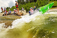 Young outdoor enthusiasts learn the art of whitewater kayaking during a summer camp session at the US National Whitewater Center (USNWC) in Charlotte NC. The USNWC is home to one of the world's largest manmade recirculating whitewater courses. The boy on the green kayak in this photo is model released. Others in photo are not.