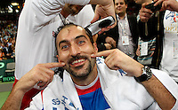 Nenad Zimonjic, center, of Serbia, gets a celebratory haircut on the court, right after the Serbian national tennis team won the Davis Cup finals against France in Belgrade, Serbia, Sunday, Dec. 5, 2010..(Srdjan Stevanovic/Starsportphoto ©)