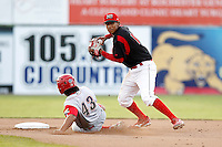 Batavia Muckdogs shortstop Cesar Valera #14 attempts to turn a double play as Peter Lavin #43 slides in during the second game of a doubleheader against the Williamsport Crosscutters at Dwyer Stadium on August 23, 2011 in Batavia, New York.  Batavia defeated Williamsport 2-1.  (Mike Janes/Four Seam Images)