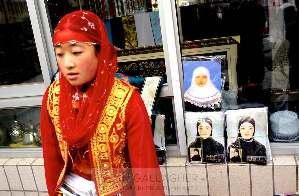 CHINA. Beijing. A woman sells traditonal Islamic dress during the festival of Eid-al-Fitr, marking the end of Ramadan. 2005