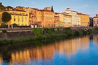 The early morning sun shines on building along the Arno River of Florence, Italy.