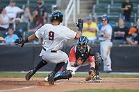 Piedmont Boll Weevils catcher Evan Skoug (9) waits for a throw as Jose Almonte (9) of the Hickory Crawdads approaches home plate at Kannapolis Intimidators Stadium on May 3, 2019 in Kannapolis, North Carolina. The Boll Weevils defeated the Crawdads 4-3. (Brian Westerholt/Four Seam Images)