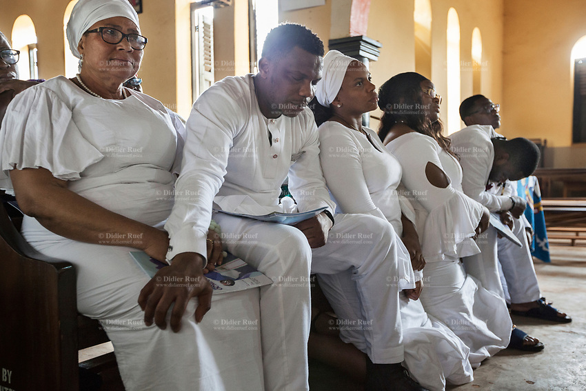 Nigeria. Enugu State. Ukana. Saint Joseph's Catholic Parish. Igbo funeral of Dr William Ikechukwu who passed away at the age of 68 years old. The family of the deceased man is sitting on the first row and is dressed in white clothes. The wife is crying and her older son is holding her hands. All women wear a head tie which is a women's cloth head scarf. The head tie is used as an ornamental head covering or fashion accessory, or for functionality in different settings. Its use or meaning can vary depending on the country and/or religion of those who wear it. The head tie is called gele in Nigeria. 5.07.19 © 2019 Didier Ruef