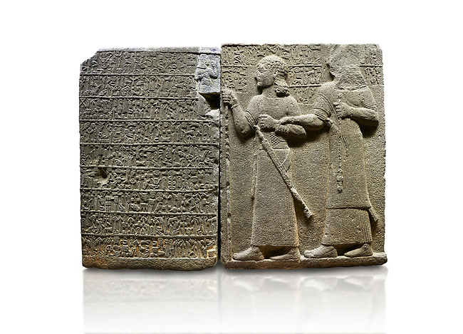 """Hittite monumental relief sculpted orthostat stone panel of Royal Buttress. Basalt, Karkamıs, (Kargamıs), Carchemish (Karkemish), 900-700 B.C. Anatolian Civilisations Museum, Ankara, Turkey.<br /> <br /> Hieroglyph panel (left) - Discourse of Yariris. Yariris presents his predecessor, the eldest son Kamanis, to his people. <br /> Right Panel - King Araras holds his son Kamanis from the wrist. King carries a sceptre in his hand and a sword at his waist while the prince leans on a stick and carries a sword on his shoulder. <br /> <br /> Hieroglyphs reads; """"This is Kamanis and his siblings.) held his hand and despite the fact that he is a child, I located him on the temple. This is Yariris' image"""".  <br /> <br /> Against a white background."""