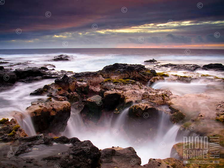A blowhole along the Big Island's Keahole Point coastline at sunset.
