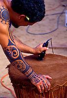 A tattooed Hawaiian man shaves the head of a newly made pahu (drum).