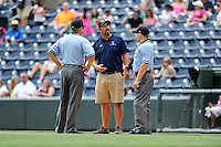 Head groundskeeper Greg Burgess of the Greenville Drive, center, discusses the impending bad weather with umpires Chris Scott, left, and Jonathan Parra on Sunday, June 14, 2015, at Fluor Field at the West End in Greenville, South Carolina. Greenville won, 10-8. (Tom Priddy/Four Seam Images)