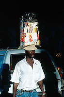 Haiti. Province of Ouest. Port-Au-Prince. Downtown. Market area. Daily life for a jobless man. Informal economy. The man carries on his head in a large plastic bag drugs which he sells in the streets in order to make some money to feed his family.  © 2003 Didier Ruef