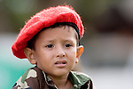 "A Venezuelan boy, wearing a version of President Hugo Chavez's trademark red beret, watches a military parade in Valencia, Venezuela, on Saturday, June 24, 2006. The military parade was to celebrate Army Day and took place in ""Campo de Carabobo"", the field where the last big battle for the Venezuelan independence was won. (ALTERPHOTOS/Alvaro Hernandez)."