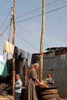 Addis Abeba, Etiopia. Lungo le strade periferche. Panni appesi e donna prepara la farina.In a secondary street woman prepare food.