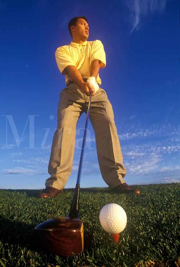 Male golfer teeing off.