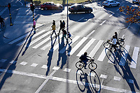 SWEDEN, Stockholm, traffic at Kvarteret Sländan, crosswalk zebra stripes at street crossing with pedestrian, bicycle driver and cars
