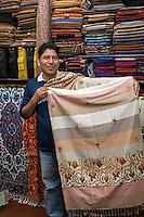 Nepal, Kathmandu.  Fabric Vendor Shows his Wares.
