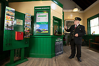 BNPS.co.uk (01202) 558833. <br /> Pic: CorinMesser/BNPS<br /> <br /> Pictured: Corfe Castle Station Master Peter Brice checks the time on his pocket watch, the watch used by the guard on Winston Churchill's funeral train, against the new information boards. <br /> <br /> One of Britain's most popular heritage railways has been given a 21st century update with new digital screens giving steam train passengers real time information.<br /> <br /> Swanage Railway in Dorset has become the first heritage railway in the country to unveil new digital information boards.<br /> <br /> The screens will be housed in traditional 1950s notice board-style frames to keep the modern technology in keeping with its vintage surroundings.
