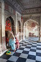 India, Dehradun.  A Women Praying at the Sikh Durbar Shri Guru Ram Rai Ji Maharaj Temple, built in 1707.  Visitors tie bits of red cloth to the window latticework as a symbol of prayers offered.