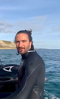 BNPS.co.uk (01202) 558833 <br /> Pic: OlyRush/BNPS<br /> <br /> WITH VIDEO - https://youtu.be/jhqAYGSjKAk<br /> <br /> Pictured: Joe Wicks is shipped back to shore after being rescued by Oly and his clean Jurassic Coast team.<br /> <br /> Bodycoach superstar Joe Wicks had 'his life saved' by an environmental campaigner after his jet board broke down and he became stranded on rocks at a beauty spot.<br /> <br /> The Youtube sensation got into difficulties while visiting idyllic Lulworth in Dorset with his wife, Rosie, to celebrate his 36th birthday.<br /> <br /> The pair went out to sea on their boards but Joe's board's engine flooded, forcing him to scramble onto nearby rocks.<br /> <br /> He frantically waved to a passing boat for help and was spotted by Oly Rush on his vessel Sea Rex, who was cleaning the coastline with his team.<br /> <br /> Wicks swam out to Oly's boat and was taken to safety following the dramatic incident on the Jurassic Coast.