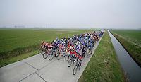 Peloton racing through the windy Moeren landscape<br /> <br /> Handzame Classic 2015